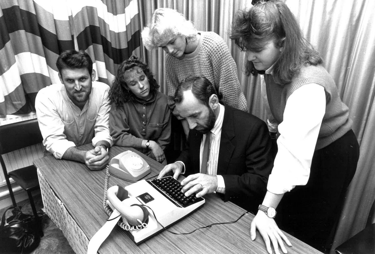 Staff gather around to look at a TTY device. It resembles a typewriter with a phone receiver on the top. Victorian Deaf Society established Australia's first TTY relay service (circa 1980).